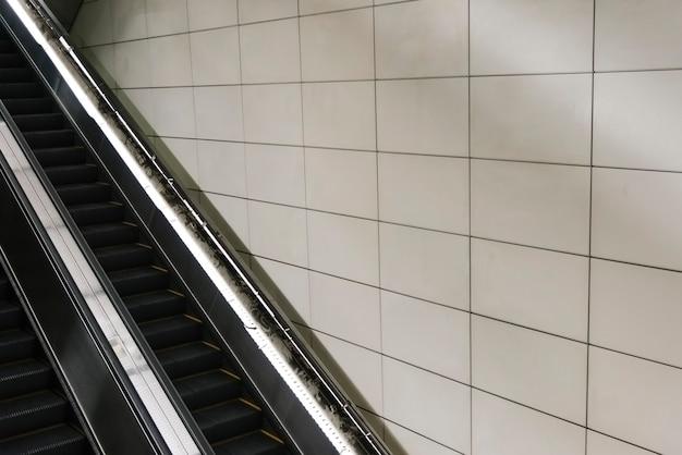 Escada rolante com parede de azulejos em branco Foto gratuita