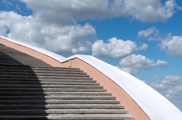 Escadaria concreta contra o céu azul e as nuvens. Foto Premium