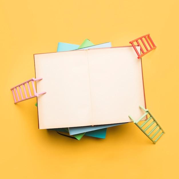 Escadas coloridas, apoiando-se no caderno aberto Foto gratuita