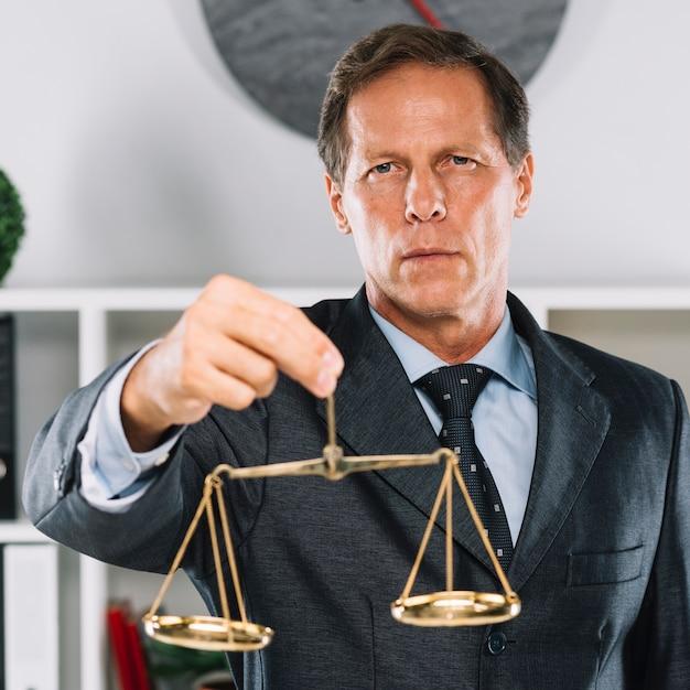 Escala de justiça dourada atrás do advogado que assina o documento na mesa Foto gratuita