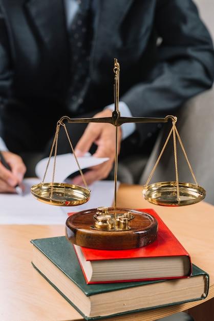 Escala de justiça dourada na pilha de livro na frente do advogado, assinando o documento Foto gratuita