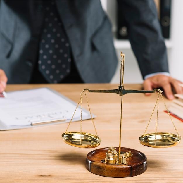 Escala de justiça por trás do advogado, assinando o documento na mesa Foto gratuita