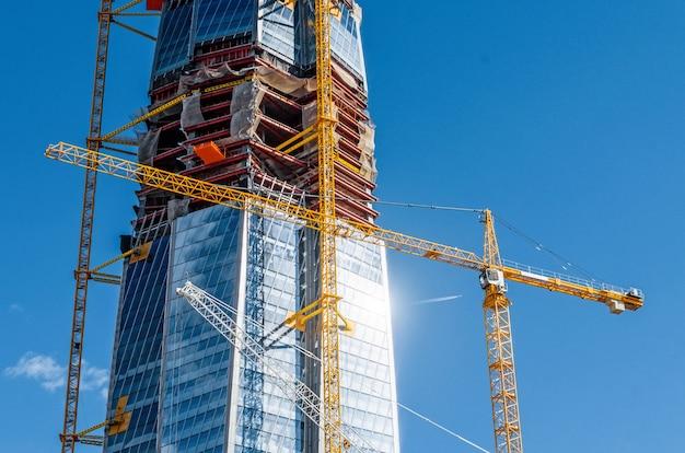 Escale o edifício ativo dos arranha-céus, brilhe o sol nas janelas, guindastes contra o céu azul. Foto Premium