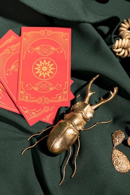 Escaravelho de ouro ao lado de cartas de tarô vermelho Foto gratuita