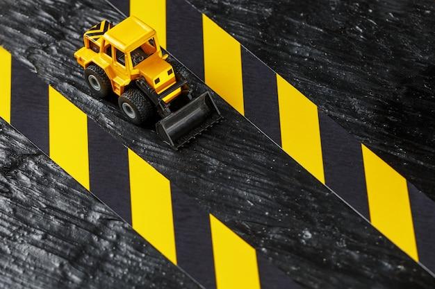 Escavadora de brinquedo amarelo. fita de vedação preta e amarela Foto Premium