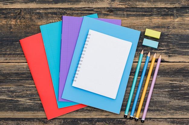 Escola após o conceito de pandemia com cadernos, lápis, etiquetas de marcador na mesa de madeira plana leigos. Foto gratuita