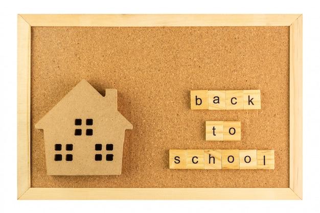 Escola de modelo pequeno e volta à palavra escola na placa de cortiça no frame de madeira, isolado no fundo branco Foto Premium