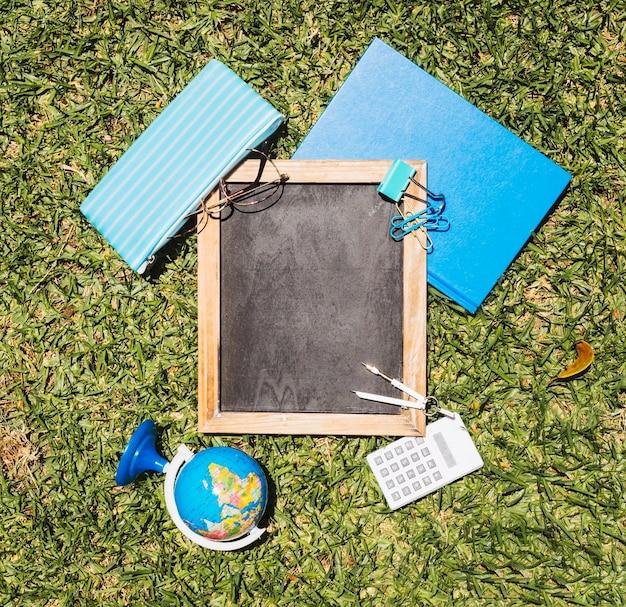 Escola de papelaria, definida no gramado verde Foto gratuita