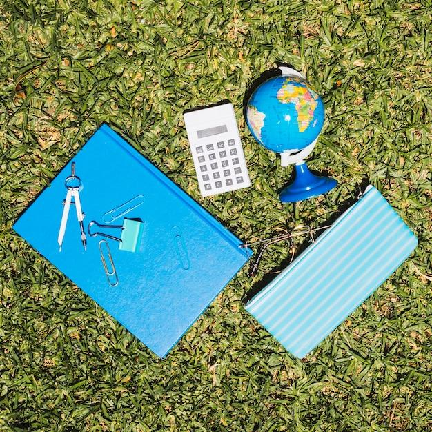 Escola de papelaria na grama Foto gratuita