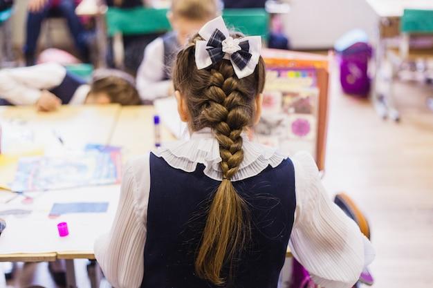 Escola e alunos, crianças escrevem e fazem o trabalho, o professor perguntou a lição, escrevendo, aprendendo novas Foto Premium