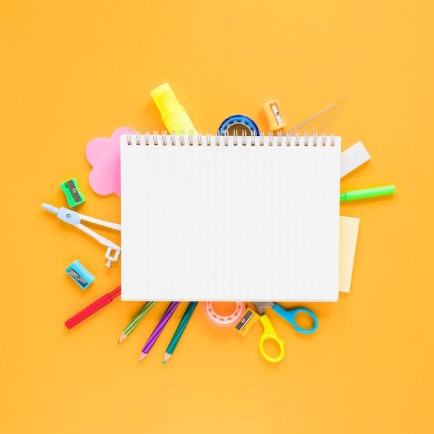 Escola e material de escritório em fundo âmbar Foto gratuita