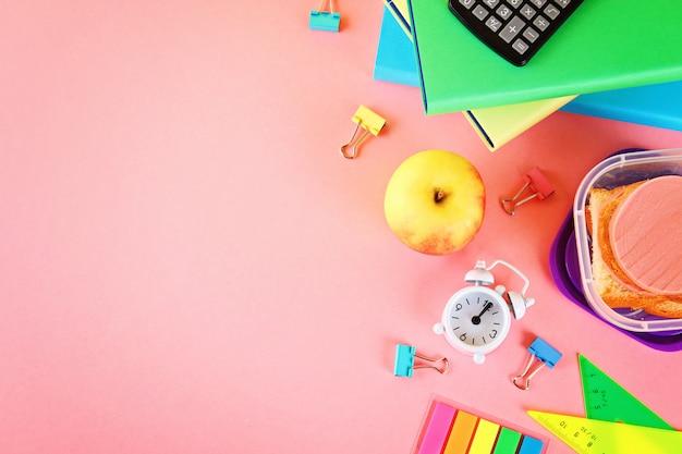 Escola e material de escritório em um fundo rosa. de volta à escola. Foto Premium