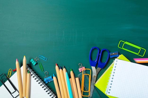Escola e material de escritório no fundo do quadro-negro Foto Premium