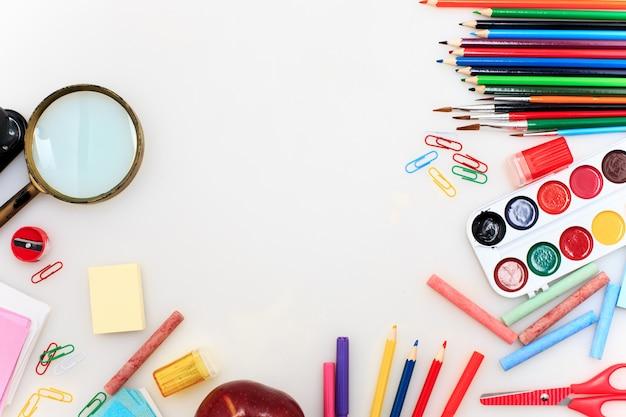 Escola em conjunto com cadernos sobre fundo branco Foto gratuita