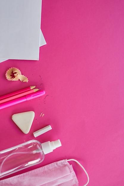 Escola plana leiga após a pandemia de coronavírus, volta às aulas em uma nova realidade, material escolar, máscara protetora e anti-séptico em um fundo rosa, espaço para texto Foto Premium
