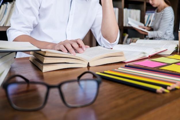 Escola secundária ou grupo de estudante universitário sentado estudando e lendo, fazendo lição de casa Foto Premium
