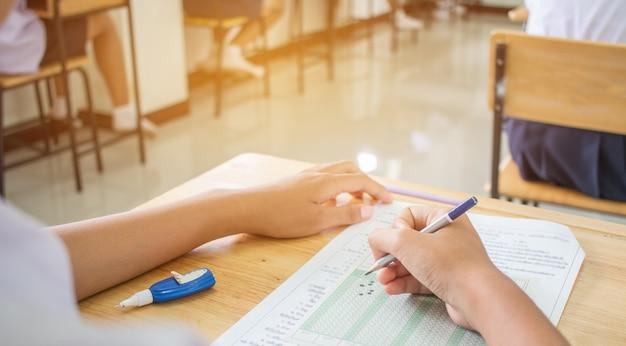 Escola uniforme estudantes asiáticos que tomam exames escrevendo resposta forma óptica com lápis Foto Premium