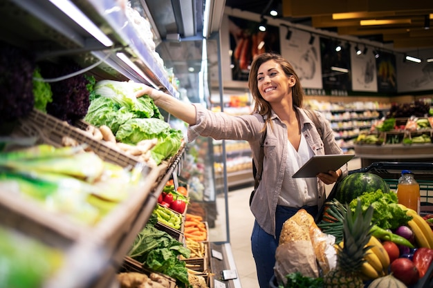 Escolhendo os melhores vegetais na prateleira do supermercado Foto gratuita