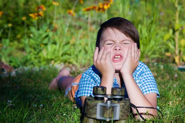 Esconde-esconde. o garoto aperta os olhos e conta até 10. o binóculo está na frente da criança Foto Premium