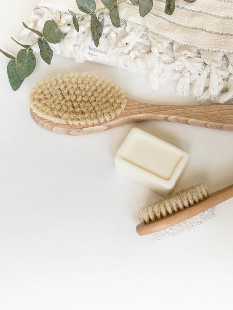Escova corporal com cabo de madeira, pedra-pomes, toalha branca e sabão em um fundo branco. vista do topo. Foto Premium