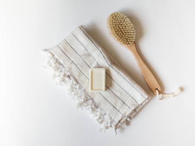 Escova corporal com cabo de madeira, toalha branca e sabão em um fundo branco. Foto Premium