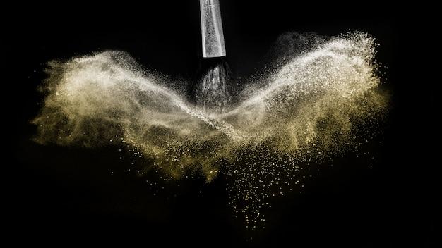 Escova cosmética com ouro em pó cosmético espalhando Foto Premium