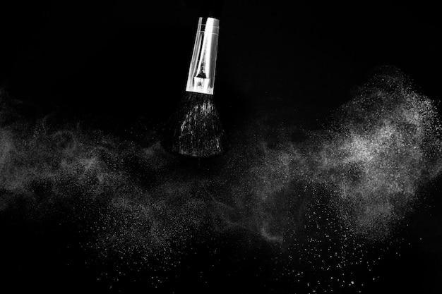 Escova cosmética com pó cosmético branco espalhando para maquiador ou design gráfico em fundo preto Foto Premium