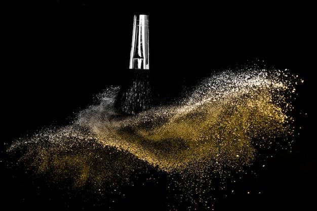 Escova cosmética com pó cosmético dourado espalhando para maquiador e design gráfico em fundo preto Foto Premium