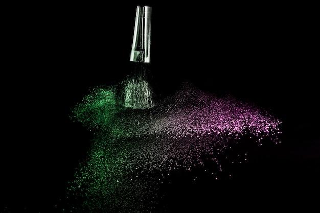 Escova cosmética com pó cosmético verde e rosa, espalhando-se para maquiador e design gráfico em fundo preto Foto Premium