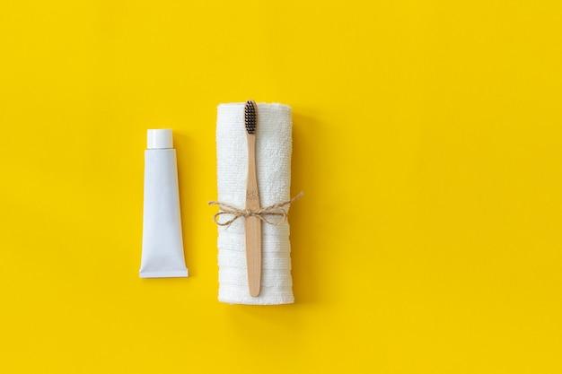 Escova de bambu eco-friendly natural na toalha branca e tubo de creme dental. Foto Premium