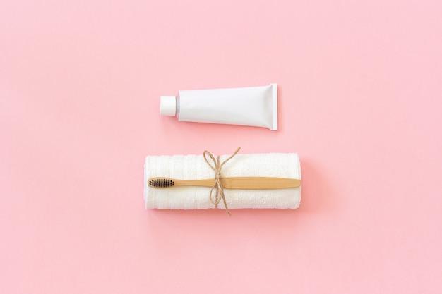 Escova de bambu eco-friendly natural na toalha branca e tubo de dentífrico. conjunto para lavar Foto Premium