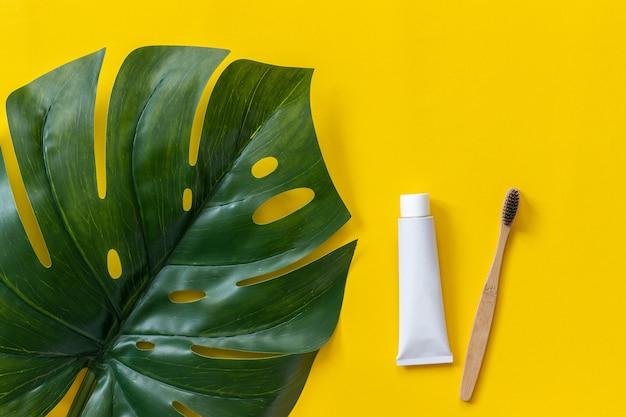 Escova de bambu eco-friendly natural, tubo de creme dental e tropical eaf monstera. conjunto para lavar Foto Premium