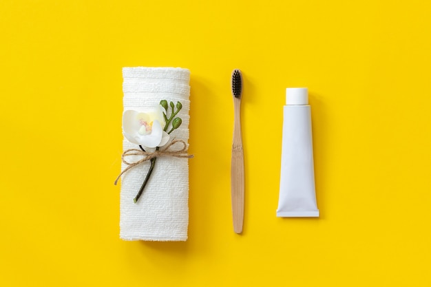 Escova de bambu natural eco-friendly, toalha branca e tubo de creme dental. conjunto para lavar Foto Premium