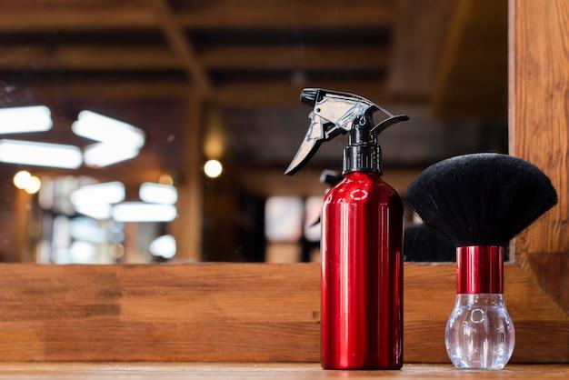 Escova de cabelo e pulverizador em um fundo desfocado Foto gratuita