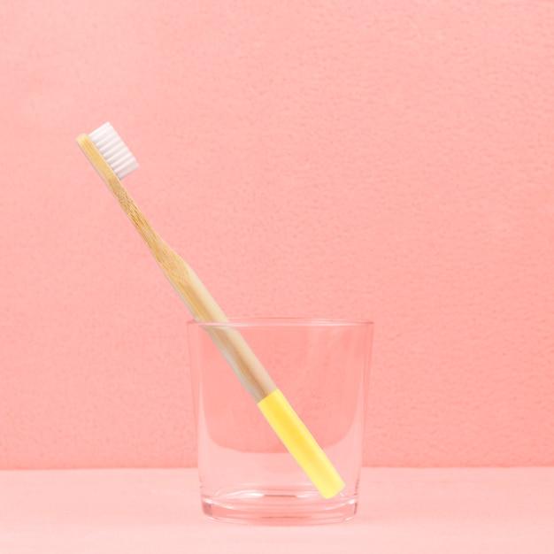 Escova de dentes de bambu eco-friendly em um vidro transparente no coral Foto Premium