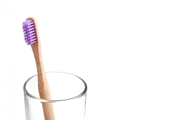 Escova de dentes de bambu em um copo Foto Premium