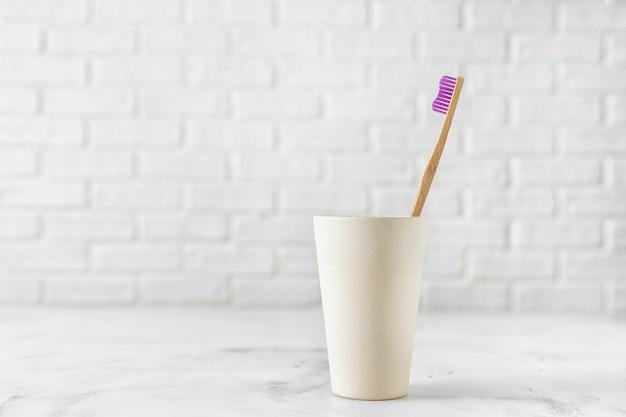 Escova de dentes de bambu no suporte no branco. Foto Premium