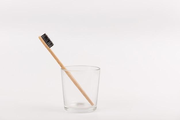 Escova de dentes de bambu no vidro no fundo branco. eco-friendly, sem plástico, sem desperdício de vida Foto Premium