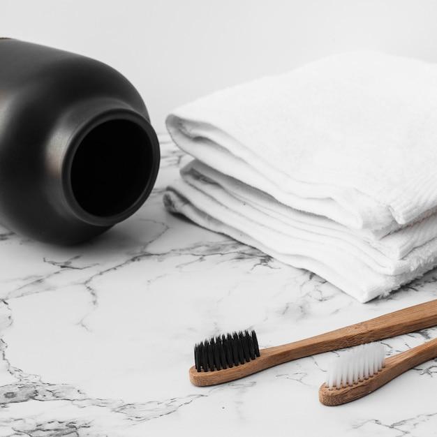Escova de dentes de madeira; toalhas brancas e jar no fundo de mármore Foto gratuita