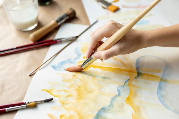 Escova de exploração de mulher de close-up e pintura Foto gratuita