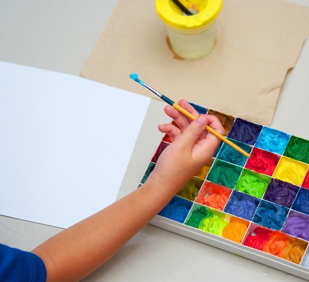 Escova de mão de criança e papel comum com paleta de cores quadrada para obras de arte, vista superior Foto Premium
