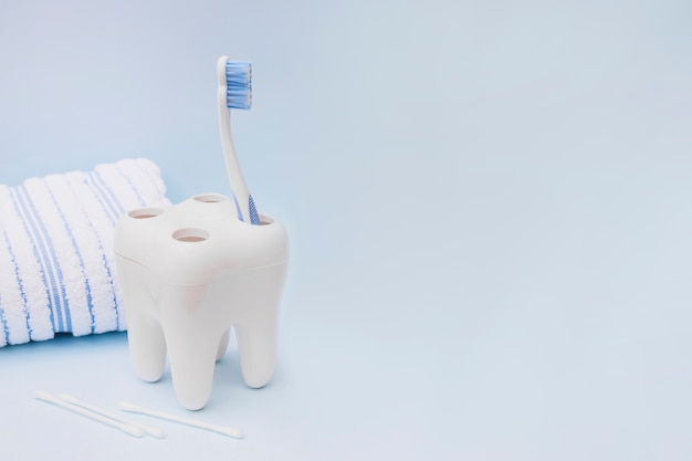 Escova dental; cotonete e toalha em fundo azul Foto Premium
