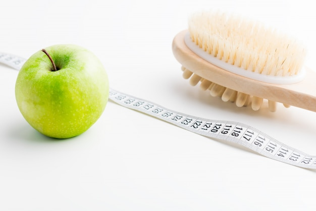 Escova seca da massagem com fita métrica e única maçã verde na mesa branca. saúde e dieta. Foto Premium