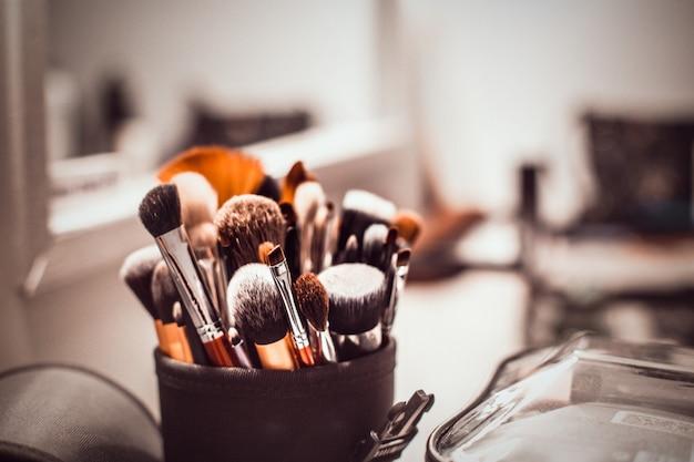 Escovas da composição-composição do artista do maquilhador e produtos cosméticos na tabela com um espelho. Foto Premium