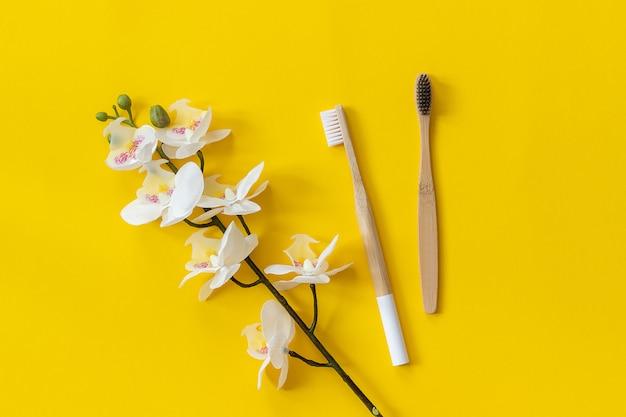 Escovas de bambu natural eco-friendly e orhid flor em papel amarelo fundo Foto Premium
