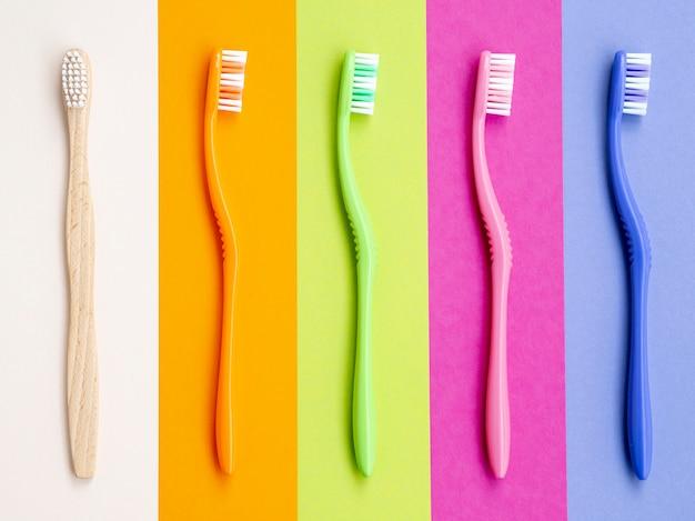 Escovas de dentes coloridas em fundo colorido Foto gratuita