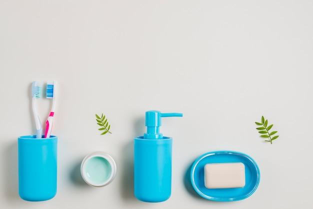 Escovas de dentes; creme; dispensador de sabão e sabão em fundo branco Foto gratuita