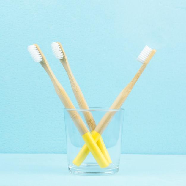 Escovas de dentes de bambu eco-friendly em um vidro transparente sobre um fundo azul Foto Premium