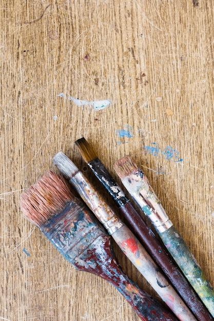 Escovas de pintura sujas velhas no contexto de madeira resistido Foto gratuita