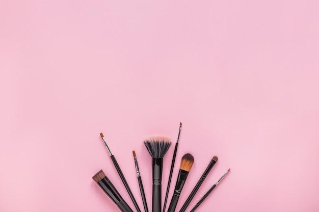 Escovas de pó diferentes na mesa-de-rosa Foto gratuita